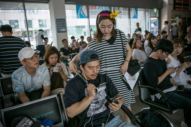Lee Jeong-hwan, foreground, and Barbie Lim (R), broadcasting jockeys for Pokemon Go Korea Facebook page, broadcast live as Lee plays the game at the Express Bus Terminal on July 15, 2016 in Sokcho, South Korea. (Photo by Jean Chung/Getty Images)