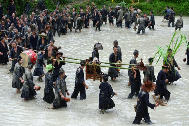 """On Saturday, September 2, 2017, local Chinese villagers gathered to celebrate a folk festival parade known as """"Dog carrying Day"""" in Jiaobang village, Gedong Town, Jianhe county, Qiandongnan Miao and Dong Autonomous Prefecture, southwest China's Guizhou province. (Photo by Imaginechina/Rex Features/Shutterstock)"""