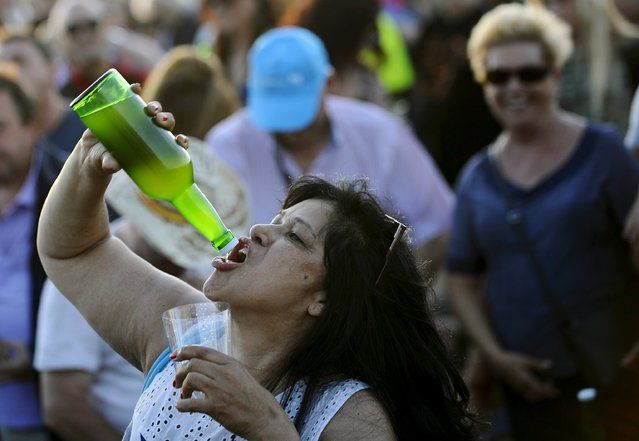 A woman drinks cider as she takes part in trying to beat the world record of people simultaneously pouring cider during the annual Fiesta de la Sidra Natural (Natural Cider Party) in Gijon, northern Spain, August 28, 2015. (Photo by Eloy Alonso/Reuters)