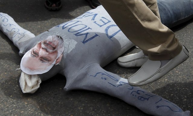 A supporter of Pakistan Muslim League (PML-Q) political party walks over an effigy depicting Indian Prime Minister Narendra Modi, during a protest to condemn the cross border firing, in Karachi, Pakistan, August 29, 2015. Cross-border firing between India and Pakistan killed at least nine people on Friday, the day India marked the 50th anniversary of a war between the two South Asian nations. (Photo by Akhtar Soomro/Reuters)