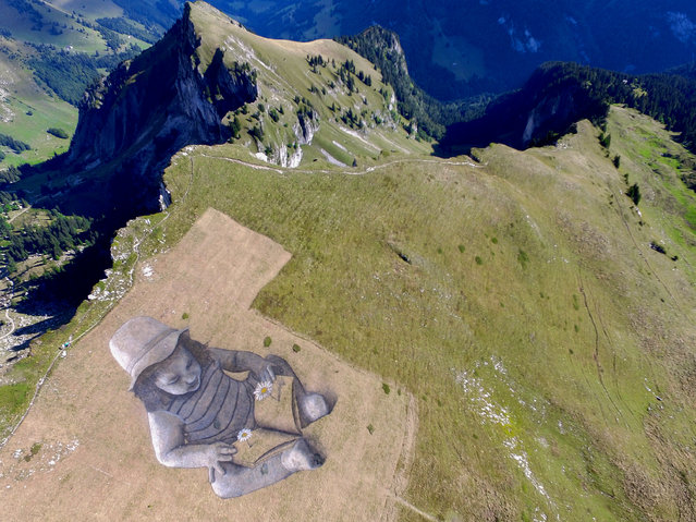 """This handout picture received from French artist Guillaume Legros is an image captured using a drone shows a general view of a land art painting by Legros (also known as Sapye)  measuring some 6,000 square metres and entitled """"A story of the future"""" painted on a hillside in Rochers de Naye above Montreux. The giant painting was created using more that 600 litres of flour, water, milk protein and biodegradable natural pigments, and was complete to mark the occasion of 125th anniversary of the train line between Glion-Rochers de Naye. (Photo by Guillaume Legros, also known as Saype/AFP Photo)"""