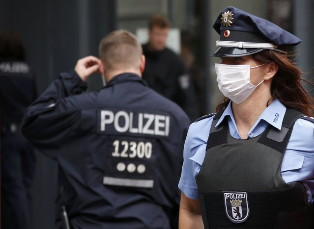 A police officer wearing a face mask stands outside the job centre in the Berlin district of Pankow August 19, 2014. A woman who showed symptoms of an infectious disease while at the job centre, was transported by emergency services to Charitie hospital on Tuesday. (Photo by Fabrizio Bensch/Reuters)