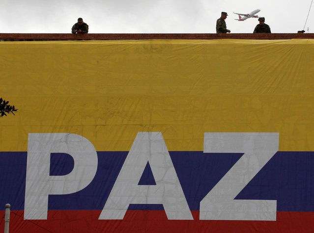 Soldiers are seen above the Colombian flag during a military parade to celebrate the 206th anniversary of Colombia's independence in Bogota, Colombia, July 20, 2016. (Photo by John Vizcaino/Reuters)