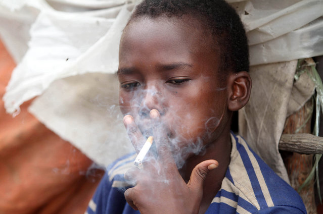Abdulahi Yaroow, 13, smokes a cigarette while chewing khat at the same time in Mogadishu August 10, 2014. (Photo by Thomas Mukoya/Reuters)