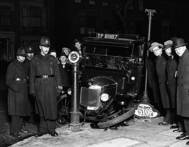 "A group of policemen and passers-by survey the wreckage of a taxi in Stoke Newington, London. Its front wheel lies on the pavement next to a sign bearing the ironic instruction ""All Cars Stop Here"". 14th February 1930. (Photo by Fox Photos)"