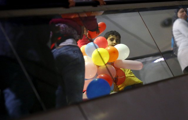 A Syrian boy holds a bunch of balloons given by wellwishers as he stands on an escalator while waiting for his registration after arriving with his family by train from Budapest's Keleti station at the railway station of the airport in Frankfurt, Germany, early morning September 6, 2015. (Photo by Kai Pfaffenbach/Reuters)