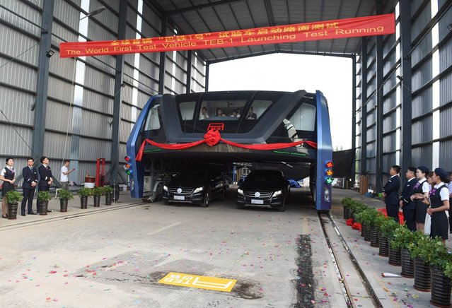The transit elevated bus TEB-1 prepares for a road test in Qinhuangdao, north China's Hebei Province, August 2, 2016. China's home-made transit elevated bus, TEB-1, conducted a road test running Tuesday. The 22-meter-long, 7.8-meter-wide and 4.8-meter-high TEB-1 can carry up to 300 passengers. The passenger compartment of this futuristic public bus rises far above other vehicles on the road, allowing cars to pass underneath. (Photo by Lo Hsziao-Kuang/Xinhua News Agency)