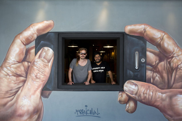 "In this September 1, 2015 photo, street artists Jenaro de Rosenzweig, left, and Alejandro Revilla pose for a portrait behind a restaurant's window covered with a mural by artist Francisco Munoz, signed with his artist's name below, in the Roma Norte neighborhood of Mexico City. Rosenzweig and Revilla founded the ""Street Art Chilango"" cooperative in March 2013, which is filling neighborhoods with public art by local street artists. (Photo by Rebecca Blackwell/AP Photo)"