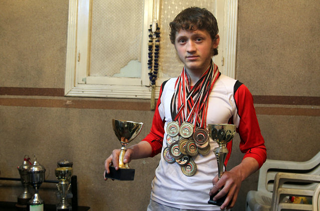 Gymnast Ahmad al-Sawas poses with his medals and trophies inside his home in the rebel-held Bustan al-Qasr neighbourhood of Aleppo, Syria March 23, 2016. (Photo by Abdalrhman Ismail/Reuters)