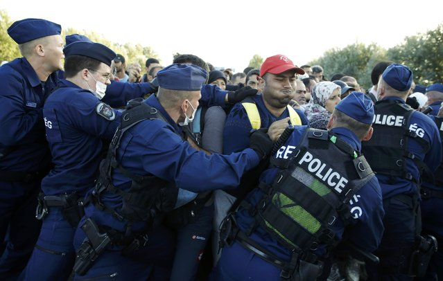Hungarian police officers push back migrants at collection point in the village of Roszke, Hungary, September 7, 201. (Photo by Marko Djurica/Reuters)