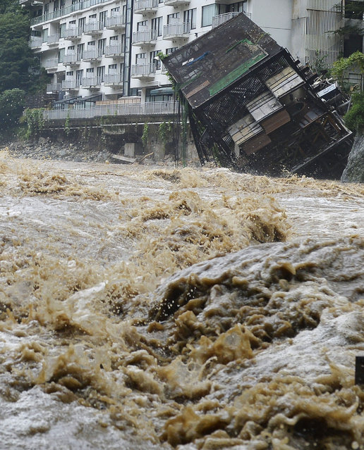 A building of an open-air spa, right, that belongs to Kinugawa Plaza Hotel, falls into the rapid stream of the Kinugawa River swollen by heavy rainfall in Nikko, Tochigi prefecture, northeast of Tokyo Thursday, September 10, 2015. (Photo by Kyodo News via AP Photo)