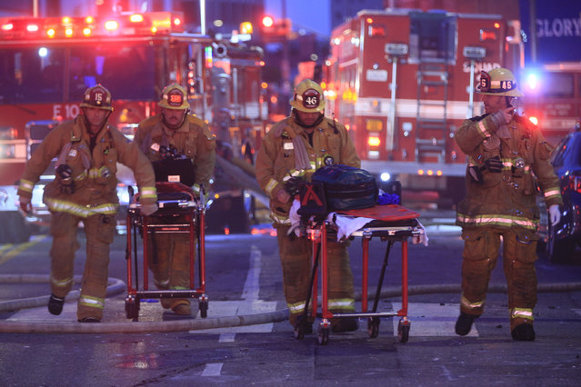 Los Angeles Fire Department firefighters push ambulance cots at the scene of a structure fire that injured multiple firefighters, according to a fire department spokesman, Saturday, May 16, 2020, in Los Angeles. (Photo by Damian Dovarganes/AP Photo)