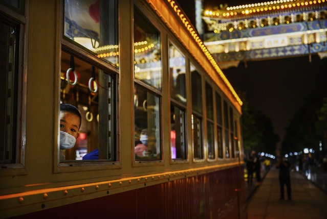 A Chinese boy wears a protective mask as he rides in a streetcar in a tourist and commercial area on May 16, 2020 in Beijing, China. After decades of growth, officials recently said Chinas economy had shrunk in the latest quarter due to the impact of the coronavirus epidemic. The slump in the worlds second largest economy is regarded as a sign of difficult times ahead for the global economy. While industrial sectors in China are showing signs of reviving production, a majority of private companies are operating at only 50% capacity, according to analysts. With the pandemic hitting hard across the world, officially the number of coronavirus cases in China is dwindling, ever since the government imposed sweeping measures to keep the disease from spreading. Officials believe the worst appears to be over in China, though there are concerns of another wave of infections as the government attempts to reboot the worlds second largest economy. Since January, China has recorded more than 81,000 cases of COVID-19 and over 4000 deaths, mostly in and around the city of Wuhan, in central Hubei province, where the outbreak first started. (Photo by Kevin Frayer/Getty Images)