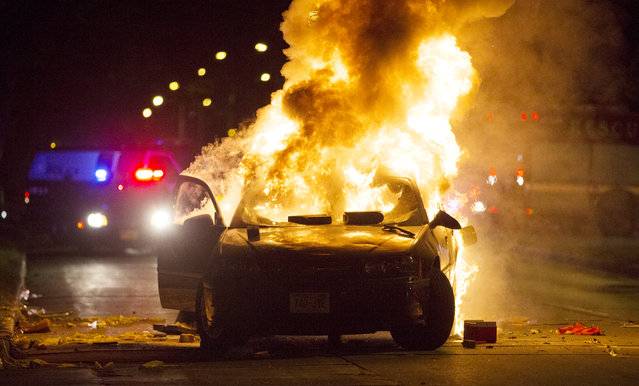 A car burns as a crowd of more than 100 people gathers following the fatal shooting of a man in Milwaukee, Saturday, August 13, 2016. The Milwaukee Journal Sentinel reported that officers got in their cars to leave at one point, and some in the crowd started smashing a squad car's window, and another vehicle, pictured, was set on fire. The gathering occurred in the neighborhood where a Milwaukee officer shot and killed a man police say was armed hours earlier during a foot chase. (Photo by Calvin Mattheis/Milwaukee Journal-Sentinel via AP Photo)