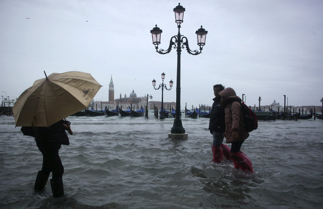 People walk through a flooded street during a period of seasonal high water in Venice November 11, 2012. The water level in the canal city rose to 149 cm (59 inches) above normal, according to local monitoring institute Center Weather Warnings and Tides. (Photo by Manuel Silvestri/Reuters)