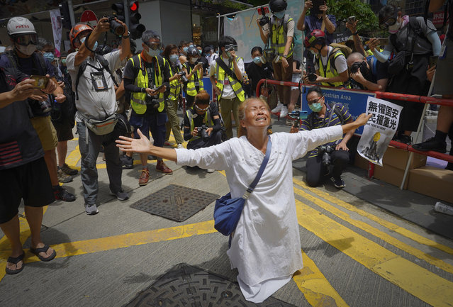 A woman prays in front of police at Causeway Bay before the annual handover march in Hong Kong, Wednesday, July 1, 2020. (Photo by Vincent Yu/AP Photo)