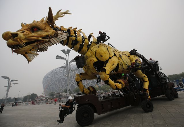 """A mechanical installation named """"Long Ma"""" is operated at a rehearsal of the Long Ma performance in front of the National Stadium, also known as the Bird's Nest, in Beijing October 10, 2014. """"Long Ma"""", a 17-meter (56-ft) long and 15-meter (49-ft) tall mechanized dragon sculpture, and """"The Spider"""", a 5.7-meter (19-ft) tall and 6-meter (20-ft) wide machine, are operated by French performance art company La Machine. The structures are operated by an automatic control system and electronic equipment. (Photo by Kim Kyung-Hoon/Reuters)"""