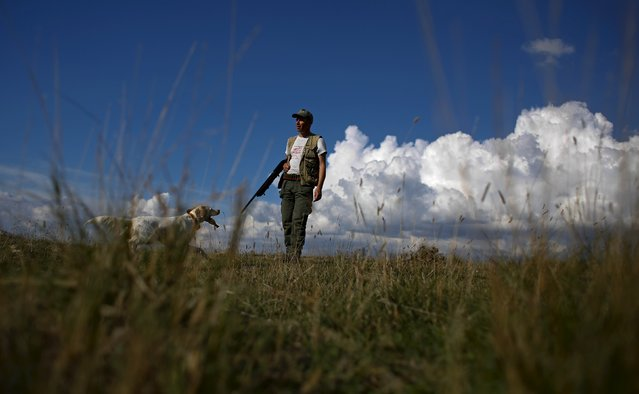 A hunter is seen next to his dog during the first day of the Italy hunting season in Castell'Azzara, Tuscany, central Italy, September 20, 2015. (Photo by Max Rossi/Reuters)