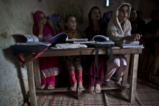 In this Tuesday, September 23, 2014, photo, Afghan refugees and internally displaced Pakistani school children attend their classes at a makeshift school on the outskirts of Islamabad, Pakistan. (Photo by Muhammed Muheisen/AP Photo)