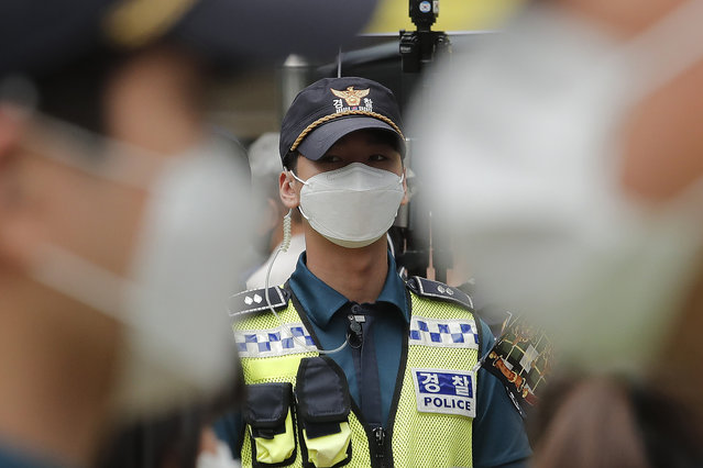 Police officers wearing face masks to help protect against the spread of the new coronavirus stand guard near the Japanese embassy in Seoul, South Korea, Wednesday, July 1, 2020. (Photo by Ahn Young-joon/AP Photo)
