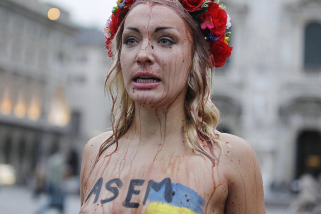 Inna Shevchenko, a member of the Ukrainian feminist protest group FEMEN, stages a protest covered with mock blood in front of the Duomo gothic cathedral in Milan, Italy, Thursday, October 16, 2014. (Photo by Luca Bruno/AP Photo)