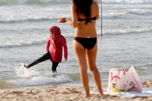 A Muslim woman wearing a Hijab kicks the water in the Mediterranean Sea as a woman wearing a bikini stands nearby at the beach in Tel Aviv, Israel August 30, 2016. (Photo by Baz Ratner/Reuters)