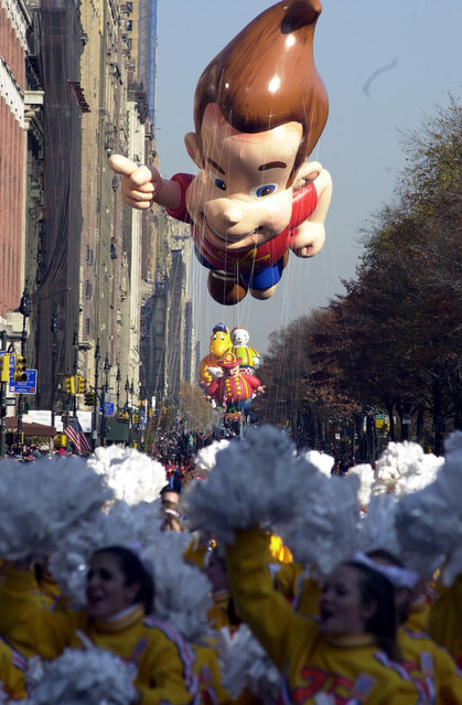 """The """"Jimmy Neutron"""" balloon floats above cheerleaders along Central Park West during the 75th annual Macy's Thanksgiving Day parade in New York, Thursday, November 22, 2001. (Photo by Mitch Jacobson/AP Photo)"""