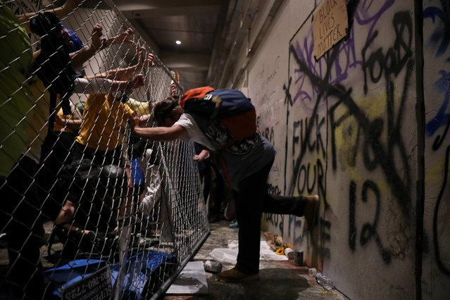 Demonstrators try to break into a federal building during a protest against racial inequality, police violence, and the presence of federal law enforcement officers, deployed under the Trump administration's new executive order to protect federal monuments and buildings in Portland, Oregon, U.S., July 21, 2020. (Photo by Caitlin Ochs/Reuters)