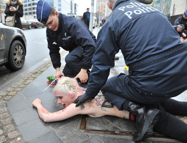 An activist of Ukraine's feminist movement Femen is taken away by the police as she demonstrates by the EU Council building where the EU-Russia summit is taking on December 21, 2012 in Brussels