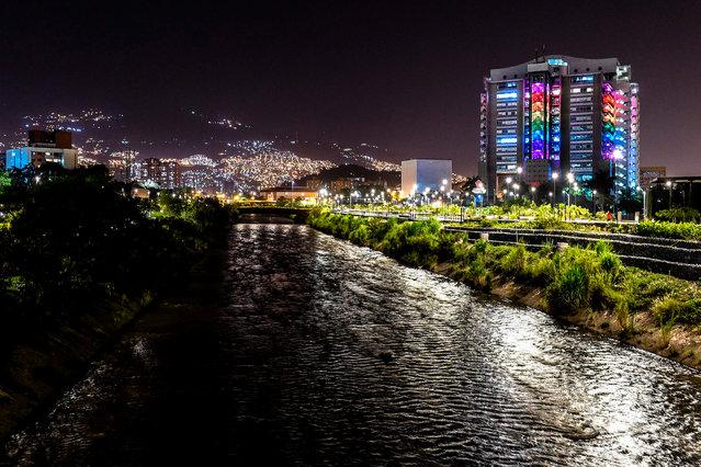 View of the Empresas Publicas de Medellin (EPM) building illuminated with rainbow colors for Pride Month, amid de COVID 19 pandemic, in Medellin, Colombia on June 24, 2020. (Photo by Joaquín Sarmiento/AFP Photo)