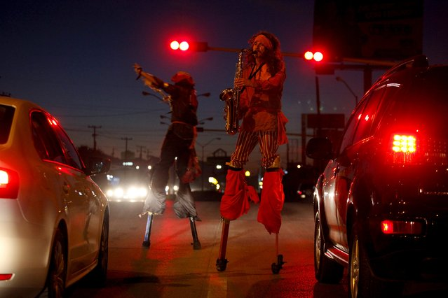 Street artists on stilts perform in front of motorists at a traffic light in Ciudad Juarez, Mexico, September 29, 2015. (Photo by Jose Luis Gonzalez/Reuters)