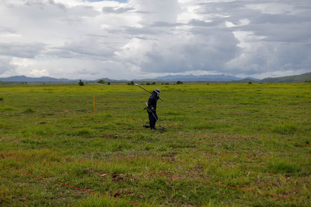 A technician from the NGO Mines Advisory Group (MAG) works in a field searching for unexploded bombs that were dropped by the U.S. Air Force planes during the Vietnam War, at Phaxay district in Xieng Khouang province, Laos September 2, 2016. (Photo by Jorge Silva/Reuters)