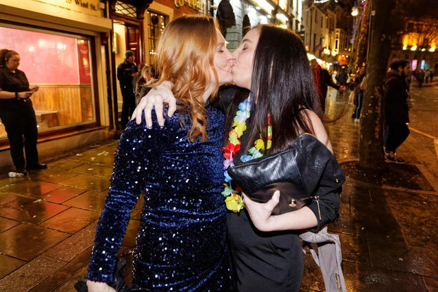 Two ladies pucker up in Swansea, Wales, England as they ring in the new year on December 31, 2017. (Photo by Athena Picture Agency)