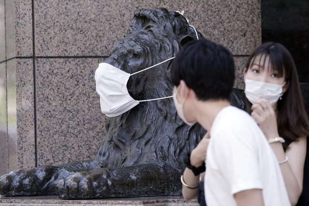A landmark lion statue of a department store placed a protective mask is seen Wednesday, August 12, 2020, in Tokyo. The Japanese capital confirmed more than 200 new coronavirus cases on Wednesday. (Photo by Eugene Hoshiko/AP Photo)