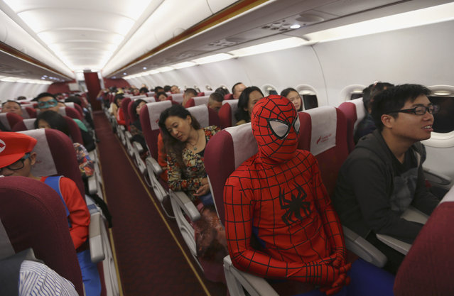A Lucky Air crew member dressed as Spiderman (3rd R) during an onboard Halloween celebration sits next to passengers during a flight from Kunming to Shenzhen, in Kunming, October 31, 2014. Attendants of the domestic Lucky Air flight on Friday night dressed themselves in costumes of superheroes and movie figures to serve their customers as well as celebrate Halloween, according to local media. (Photo by Wong Campion/Reuters)