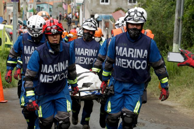 Mexican Navy rescue team members carry the body of a mudslide victim toward the coroner's truck, in Santa Catarina Pinula, on the outskirts of Guatemala City, October 4, 2015. (Photo by Josue Decavele/Reuters)