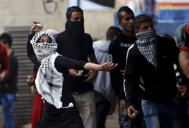 A Palestinian girl hurls stones at Israeli troops during clashes in the West Bank city of Hebron October 7, 2015. (Photo by Mussa Qawasma/Reuters)