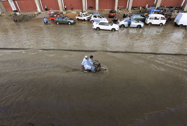 A motorcyclist drives through a flooded road after a heavy rainfall in Karachi, Pakistan, Monday, July 27, 2020. (Photo by Fareed Khan/AP Photo)