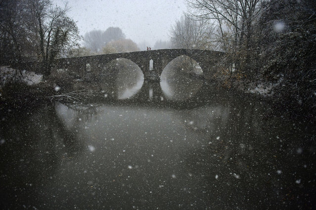 Pedestrians cross the ancient Magdalena bridge over Arga River as the first snow falls in the north of the country, in Pamplona, northern Spain, Friday, December 1, 2017. (Photo by Alvaro Barrientos/AP Photo)