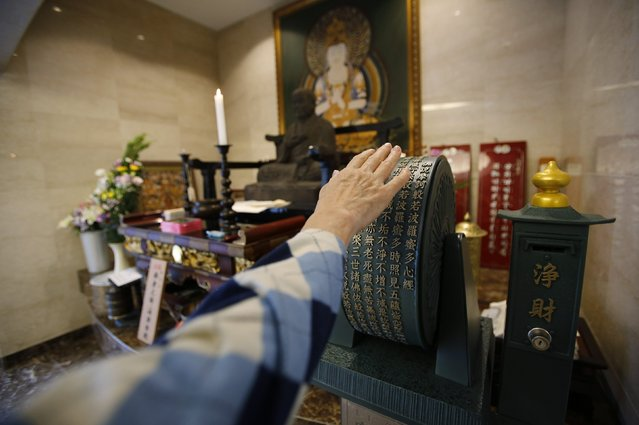 A visitor spins a prayer wheel in front of a Buddhist statue in the lobby of Ryogoku Ryoen, a multi-storey vault-style graveyard equipped with modern tombs that robotically retrieves the correct tombstone or urn based on which identity card is provided, in downtown Tokyo October 27, 2014. (Photo by Toru Hanai/Reuters)