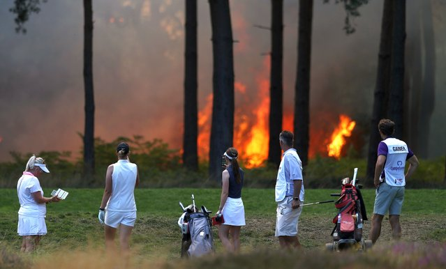 Players, Sophie Powell, Cara Gainer and Gabriella Cowley and their caddies look on as a fire nears the 10th hole during day three of The Rose Ladies Series on The West Course in the first ever ladies professional event at Wentworth Golf Club on August 07, 2020 in Virginia Water, England. (Photo by Naomi Baker/Getty Images)
