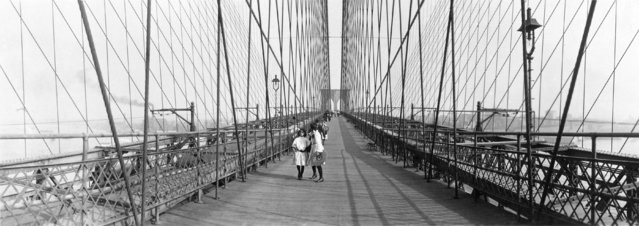 """Pedestrians on the upper deck promenade of Brooklyn Bridge, 1910"". (Photo by an unknown photographer)"