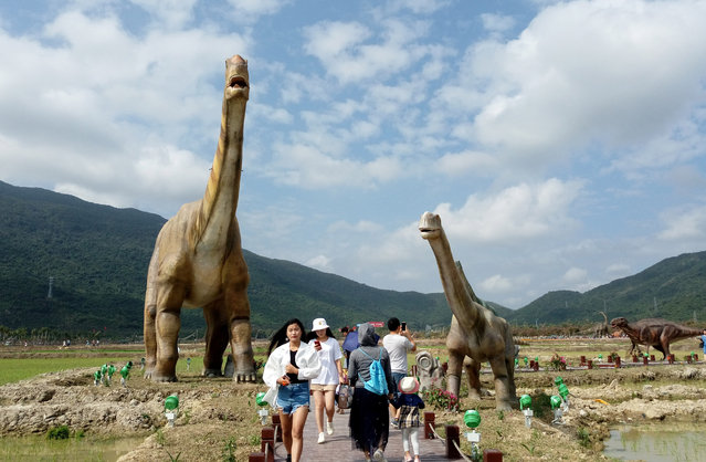 Visitors watch dinosaur models at Haitang Bay Rice Paddy Park on January 24, 2018 in Sanya, Hainan Province of China. The Haitang Bay Rice Paddy Park featuring 323 full-size dinosaur models was officially opened to the public on Thursday. (Photo by Yin Haiming/China News Service/VCG via Getty Images)
