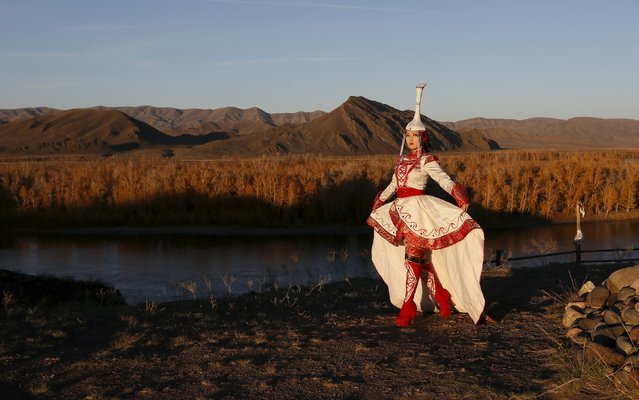 Model Choigana Kertek, dressed in traditional a costume, performs during sunset at the Aldyn Bulak area on the bank of the Yenisei River outside the village of Ust-Elegest in Tuva region, Southern Siberia, Russia, October 7, 2015. (Photo by Ilya Naymushin/Reuters)