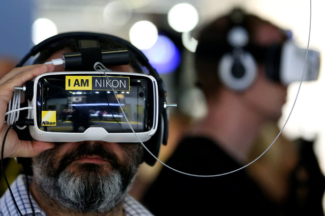 Visitors watch a virtual reality visual presentation at the Nikon booth on the Photokina, the world's largest fair for imaging in Cologne, Germany, September 20, 2016. (Photo by Fabrizio Bensch/Reuters)