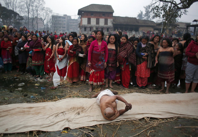A Nepalese Hindu devotee rolls on the ground as others wait to perform rituals on the last day of Madhav Narayan festival in Bhaktapur, Nepal, Wednesday, January 31, 2018. During the festival, devotees recite holy scriptures dedicated to Hindu goddess Swasthani and Lord Shiva. Unmarried women pray to get a good husband while those married pray for the longevity of their husbands by observing a month-long fast. (Photo by Niranjan Shrestha/AP Photo)
