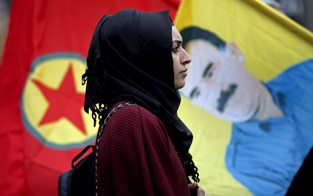 A demonstrator stands between a flag with a picture of Kurdish jailed leader Abdullah Ocalan and a flag of the Kurdistan Workers' Party (PKK) during a march to commemorate the victims of last Saturday's double suicide bombings targeting an Ankara rally of pro-Kurdish activists and civic groups, in Marseille, France, October 17, 2015. (Photo by Jean-Paul Pelissier/Reuters)