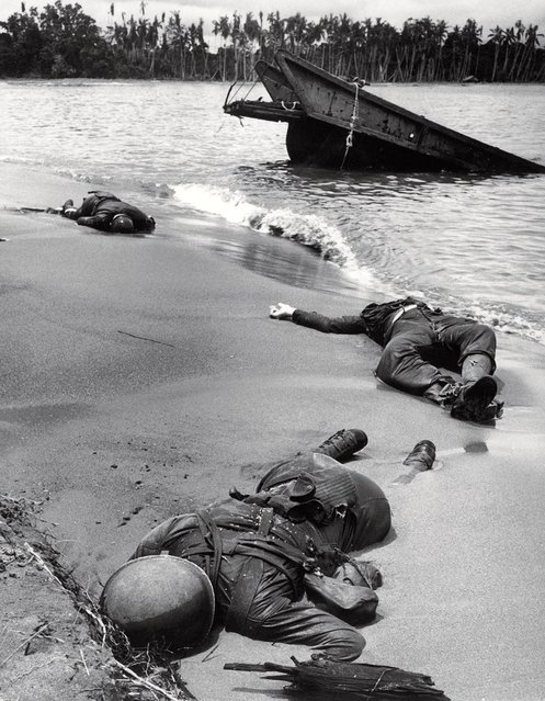 Bodies of 3 dead American soldiers lying in the sand on shoreline nr. half-sunken landing craft on Buna Beach after a Japanese ambush attack. This photo was taken in February 1943. (Photo by George Strock/Time Life Pictures)