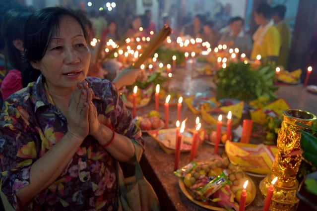 """Cambodian-Chinese pray at a temple to mark the start of the Lunar New Year in Kandal on February 16, 2018. While not a holiday in Cambodia, the Lunar New Year, the most important holiday in China and a number of countries in east and southeast Asia, began on February 16 welcoming in the """"Year of the Dog"""". (Photo by Tang Chhin Sothy/AFP Photo)"""