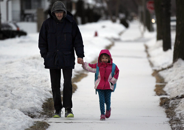 David Fine walks his 4-year old daughter Gabrelia (CQ) Fine to school along a snow covered sidewalk on S. 9th St. just north of W. Euclid Ave. in Milwaukee on Tuesday, March 12, 2013.  For those on the roads the light snow is making for a slippery ride this morning with slow travel times all around the system. (Photo by Mike De Sisti/MDESISTI@JOURNALSENTINEL.COM)